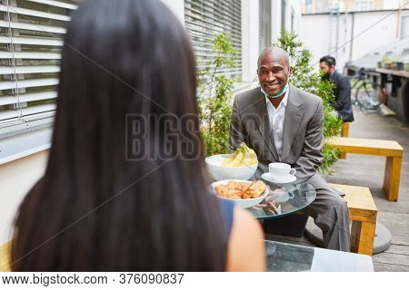 African businessman flirts with a colleague during the break in a café with a mouth guard on his chin