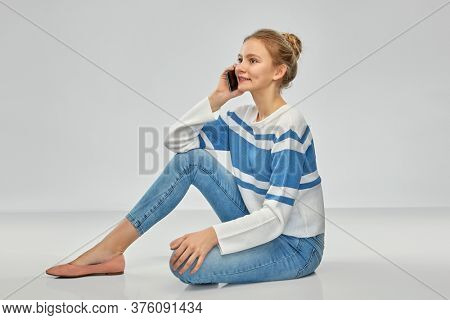 technology, communication and people concept - happy smiling teenage girl in pullover calling on smartphone sitting on floor over grey background