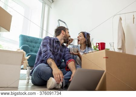 Beautiful Young Couple In Love Moving In Together, Sitting Among Cardboard Boxes In Their New Apartm