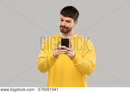 technology, communication and people concept - puzzled young man with smartphone over grey background