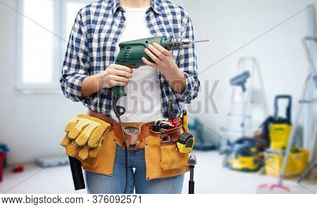 repair, construction and building concept - close up of woman or builder with working tools on belt with electric drill or perforator over utility room background