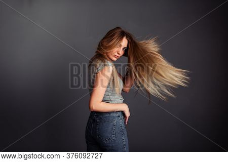 A Thin Girl In A Gray Top And Jeans With Blond Long Hair, Hand Behind Head And Looks Away Straighten