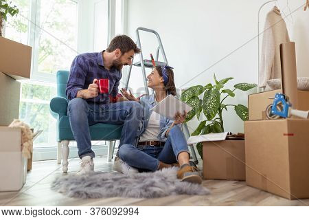 Couple In Love Drinking Coffee And Having Fun While Searching For Home Redecoration Ideas Using Tabl