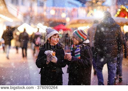 Cute Little Kids Girl And Boy Having Fun On Traditional Christmas Market During Strong Snowfall. Hap