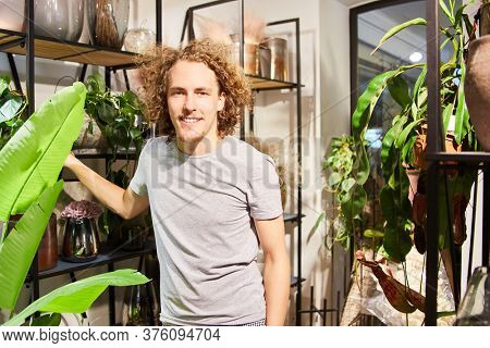Young florist as a salesman or trainee in the flower shop as a business