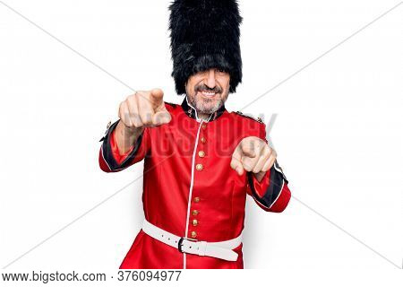 Middle age handsome wales guard man wearing traditional uniform over white background pointing to you and the camera with fingers, smiling positive and cheerful