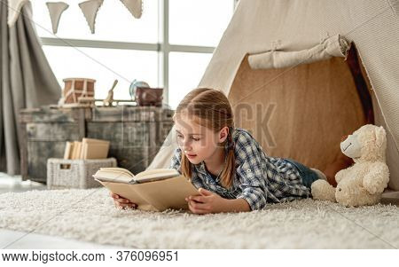 Cute little girl reading adventure book lying in wigwam settled in kids room, panoramic orientation