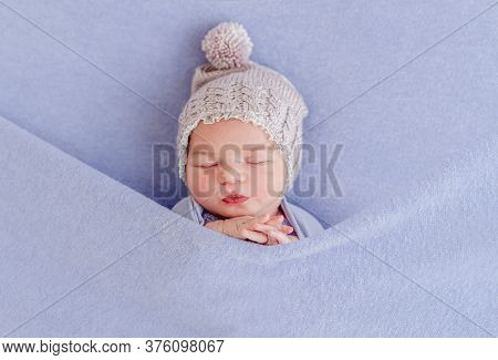 Adorable sleeping newborn covered with purple blanket
