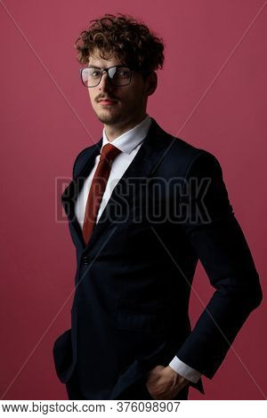 cool relaxed businessman posing with his hands in his pocket, looking at the camera, wearing a suit and glasses on pink studio background