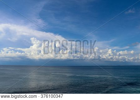 Calm Sea And Blue Sky From The Side Of A Boat With Bow Wave Wake And Cumulonimbus Clouds On The Hori