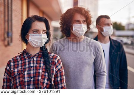 Modern Youngster Woman And Men In Casual Wear And Protective Masks Standing In Row On City Street An