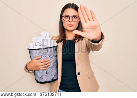 Young beautiful brunette business woman holding full paper bin of crimpled papers with open hand doing stop sign with serious and confident expression, defense gesture