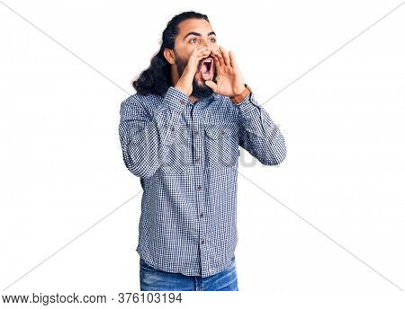 Young arab man wearing casual clothes shouting angry out loud with hands over mouth