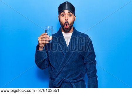 Young hispanic man wearing sleep mask and robe drinking water scared and amazed with open mouth for surprise, disbelief face
