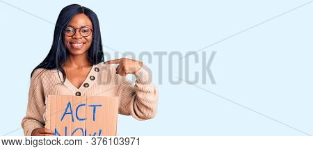 Young african american woman holding act now banner pointing finger to one self smiling happy and proud