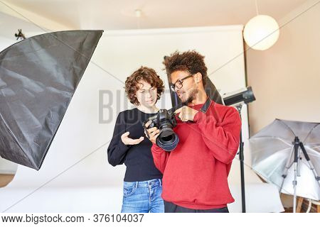 Photographer and woman as photo assistant look at the SLR camera
