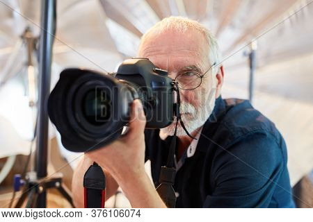 Senior as a professional photographer with SLR camera in the studio