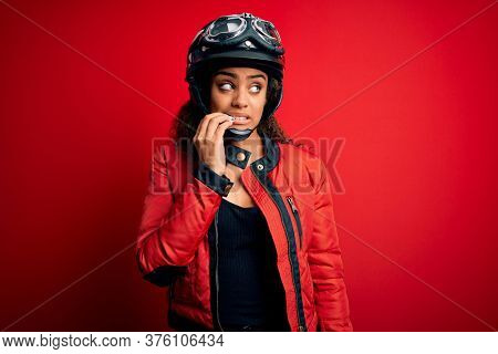Young african american motorcyclist girl wearing moto helmet and glasses over red background looking stressed and nervous with hands on mouth biting nails. Anxiety problem.