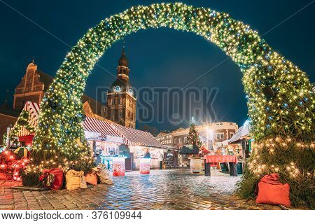 Riga, Latvia. Xmas Market On Dome Square With Riga Dome Cathedral. Christmas Tree And Trading Houses