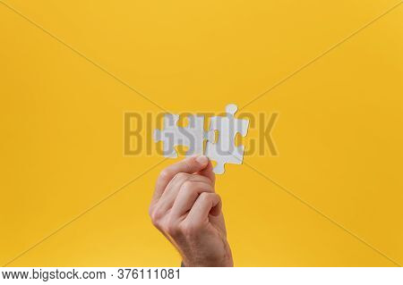 Male Hand Holding Two Matching Puzzle Pieces In His Hand In A Conceptual Image. Over Yellow Backgrou