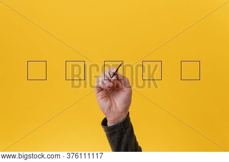 Male Hand Drawing A Check Mark In The Middle Box In A Row Of Five. Over Yellow Background.