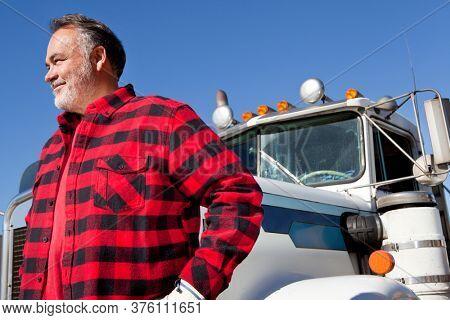 Trucker standing in front of Cargo truck