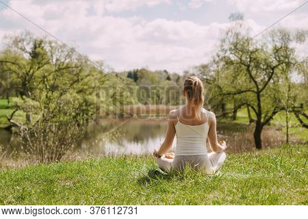 A Girl Meditates In The Lotus Position In The Fresh Air In The Park. The Girl Relaxes After Yoga. Ba