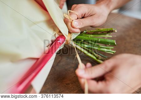 Hands of a florist are tying a bouquet with bast