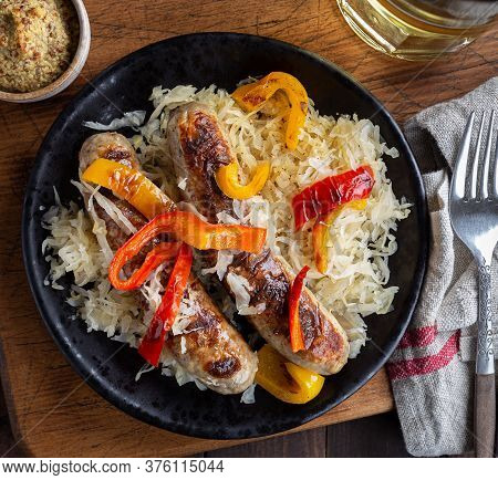 Overhead Of Grilled Bratwurst With Sauerkraut And Bell Peppers On A Plate