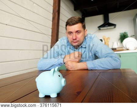 A Man Looks At The Piggy Bank. Problems With Savings, Bankruptcy Or Insolvency Concept.