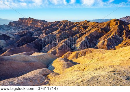 Desert at the dry lake bottom - Death Valley in California, USA. Magnificent landscape in Zabriskie Point. Picturesque multicolor sunset. The concept of active, extreme and photo tourism