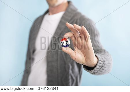 Us Elections. Unrecognizable American Citizen Holding Voting Pin On Blurred Blue Background