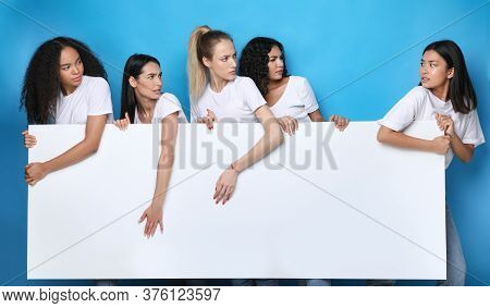 Unfriendly Girls Pulling Apart White Board For Text Standing Over Blue Studio Background. Mockup
