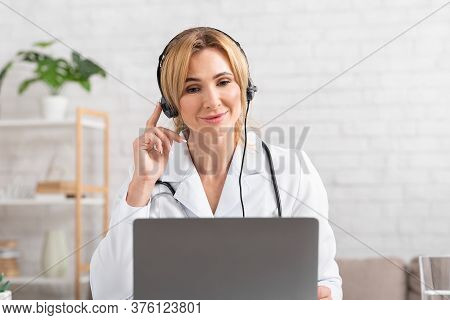 Medical Complaints. Smiling Female Doctor Holds Headphones On Head And Looks In Laptop In Office Int