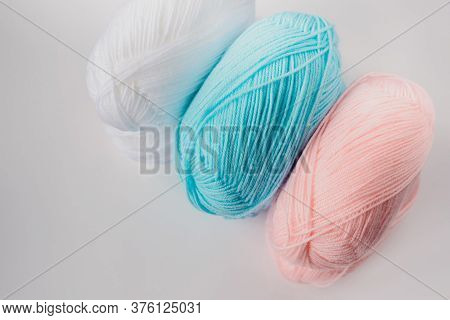Acrylic Soft Pastel Pink, Azure And White Colored Wool Yarn Thread Skeins Row On White Background, T