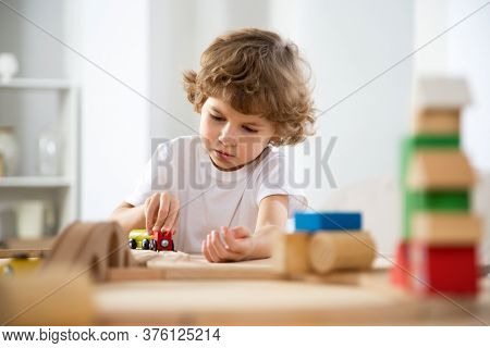 Little boy sits at a table in the playroom and plays with the constructor