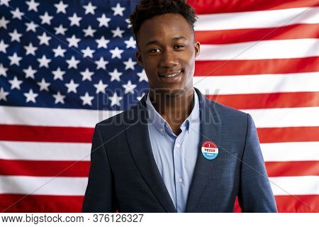 Us Presidential Election. African American Patriot Man Pinned Vote Button On Suit, Us Flag Backgroun