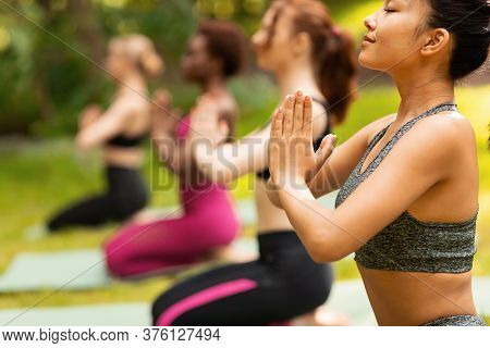 Asian Girl With Group Of Friends Meditating During Yoga Class Outside, Empty Space