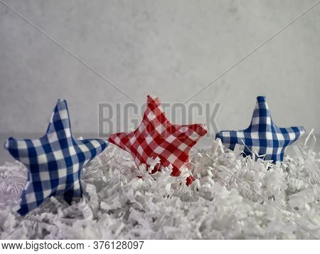 Red White And Blue Checker Fabric Covered Stars Standing Up On A Bed Of White Paper Shreds With A Pl