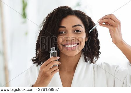 Skin Care Products. Smiling African Woman Holding Bottle With Moisturising Face Serum, Ready To Make
