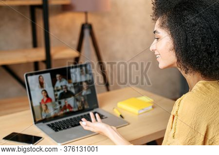Young Woman Uses App On Laptop For Video Communication With A Diverse Multiracial Group Of Coworkers