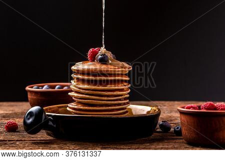 Pouring Honey On Stack Of Tasty Pancakes On Wooden Table. Homemade Classic American Pancakes With Fr