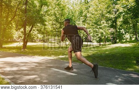 Black Sprinter Running At Park On Sunny Morning, Free Space. Panorama