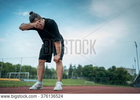 Tired And Exhauster Runner On Sport Track Outdoor