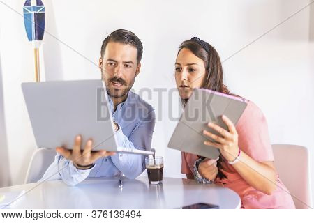 A Couple Teleworking At Home, Boy In Blue Shirt And Girl In Pink Suit. With A Laptop And Tablet From