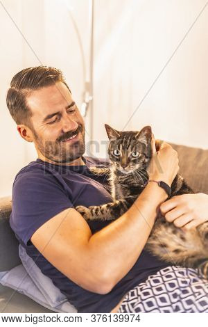 A Young Dark-haired Caucasian In A Blue Shirt With His Lovely Gray And White Domestic Cat. The Cat M