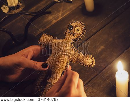 Voodoo Doll In Womens Hand Pierced With Many Needles, As A Symbol Of Revenge And Causing Harm To Peo
