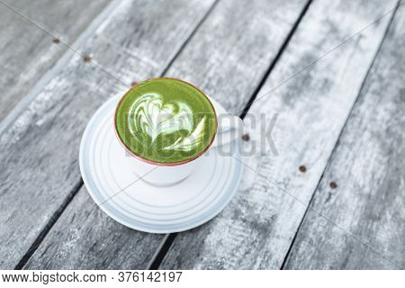 Cup Of Fresh Green Matcha Latte Beverage With Latte Art On Foam. Background Of Wooden Table With Gra