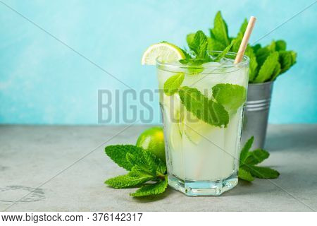 Homemade Lemonade Or Mojito Cocktail With Lime, Mint And Ice Cubes In A Glass On A Wooden Rustic Tab