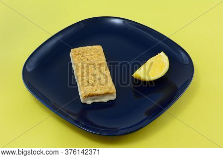 Lemon Rind Oat Bar With Icing And Lemon Wedge On Blue Snack Plate
